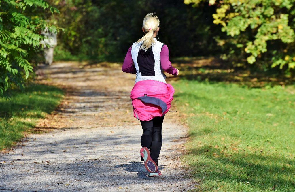 femme qui court sur un chemin de forêt