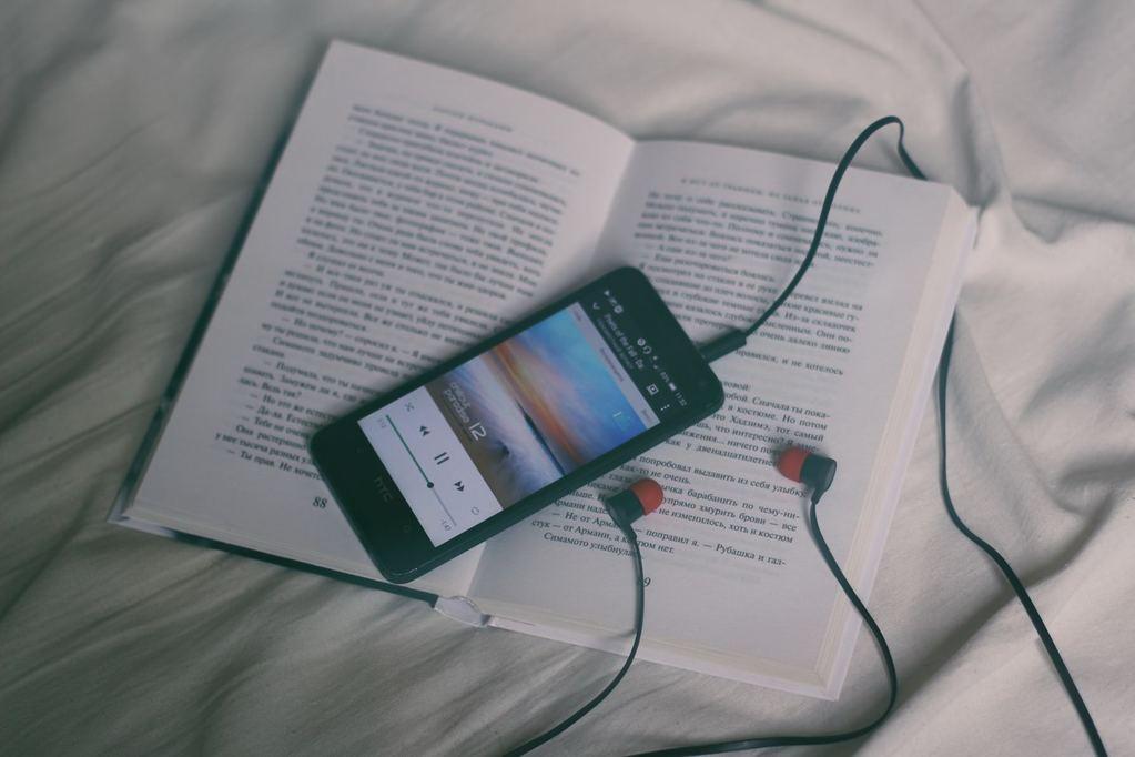 livre et téléphone avec écouteur posé sur le lit