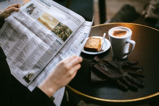 une personne lit une journal dans un café