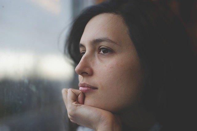 femme qui réfléchit au bord d'une fenetre