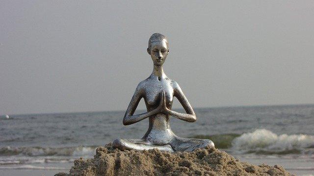 figurine de yoga sur sable devant la mer